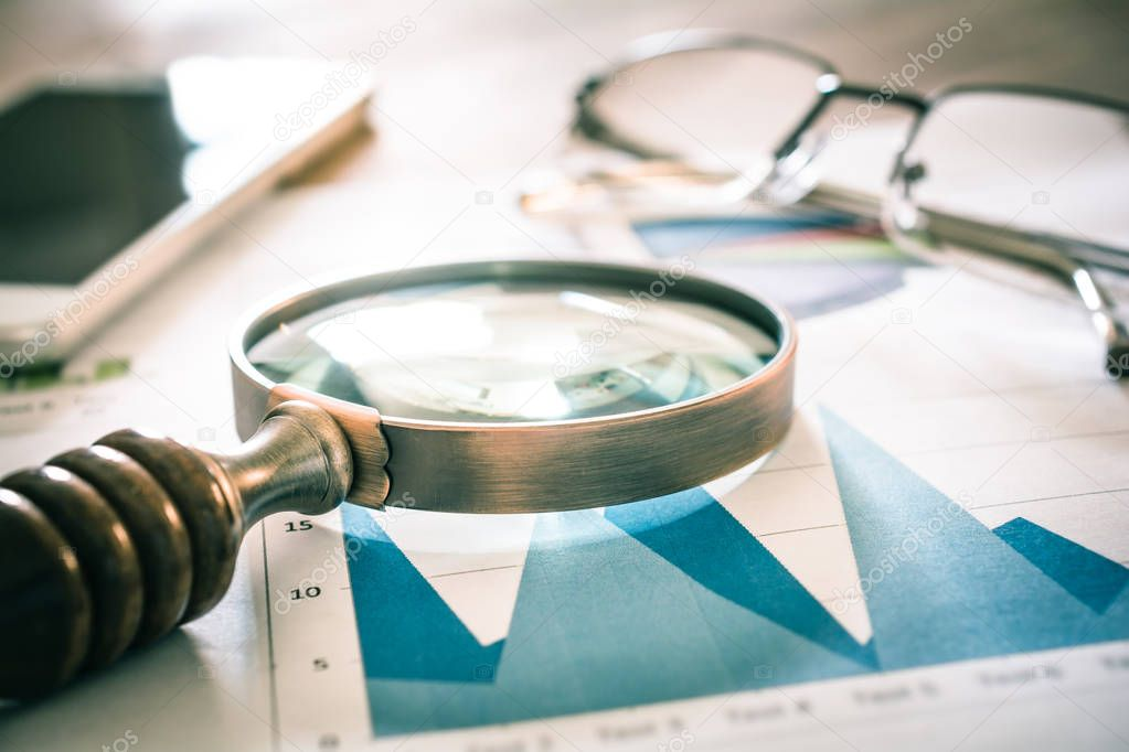 Analyzing Business Statistics With A Vintage Magnifying Glass, Mobile Phone And Eyeglasses