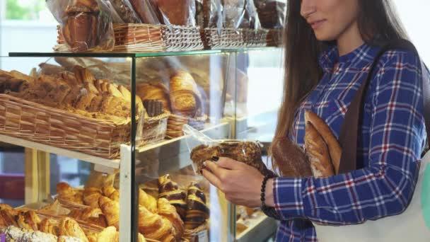 Vágott lövés egy női ügyfél megvizsgálja a csomag a cookie-kat a pékség