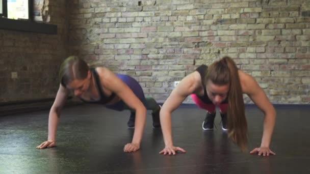 Sportovkyně vysoký podání po dělá push up společně