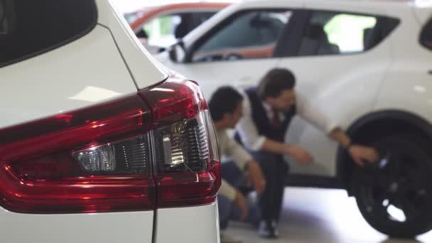 Prodejce aut a jeho mužské klient diskusi pneumatiky auta na prodej