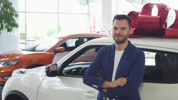 Mladý šťastný muž s úsměvem zobrazeno klíčky k jeho nové auto