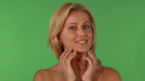 Studiový portrét krásné zralé ženy dotýká její tvář smyslně