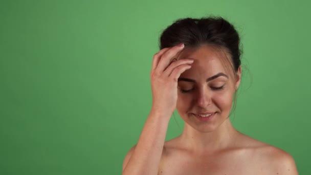 Krásná šťastná žena pózuje hravě na zelené chromakey