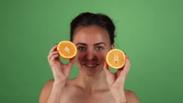 Gorgeous happy female smiling holding oranges on green chromakey