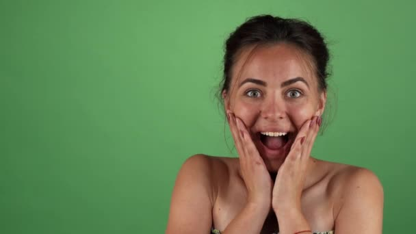 Attractive woman looking surprised on green chromakey background
