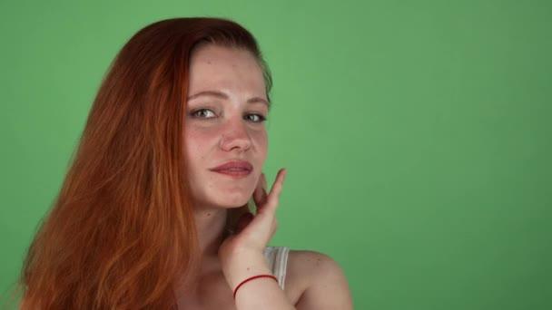 Nádherná žena s dlouhé nazrzlé vlasy pózuje na zeleném pozadí