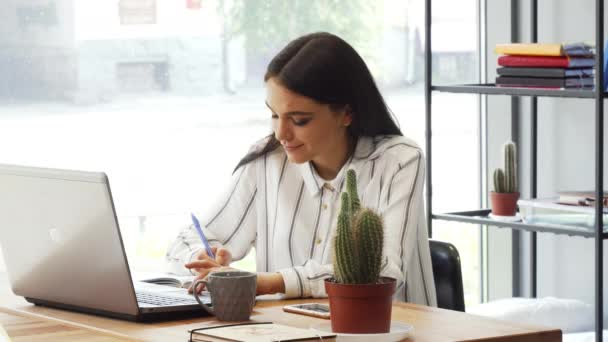 Attractive young businesswoman enjoying working at her office