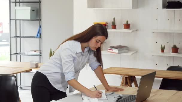 Female designer busy at the office, working on her laptop