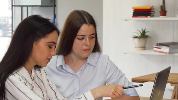 Two female designers working on a laptop together