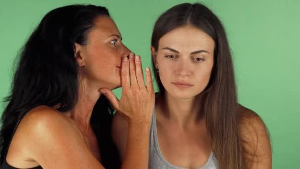 Mladá žena hledá šokován, zatímco její přátelé, šeptal jí