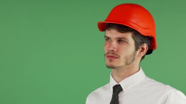 Handsome male constructionist in a hardhat looking away thoughtfully