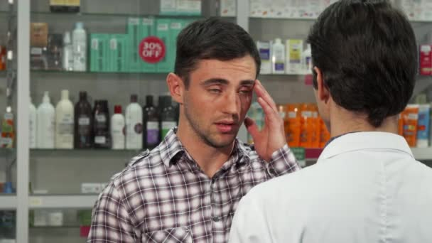 Young handsome man having headache talking to the pharmacist while shopping for painkillers at the local drugstore. Male customer with migraine buying medications.