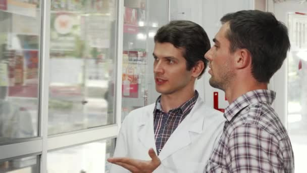 Cheerful pharmacist helping male customer choosing products to buy