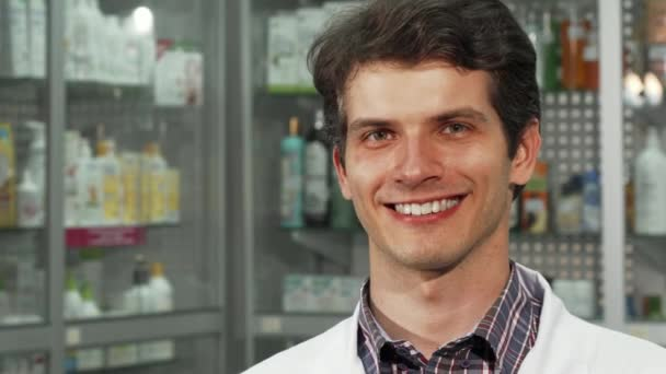 Cheerful male chemist smiling holding two blisters of pills