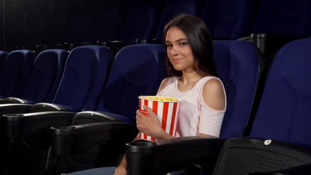 schöne glückliche Frau, die im Kino in die Kamera lächelt