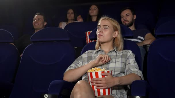 Young attractive woman smiling showing thumbs up at the cinema