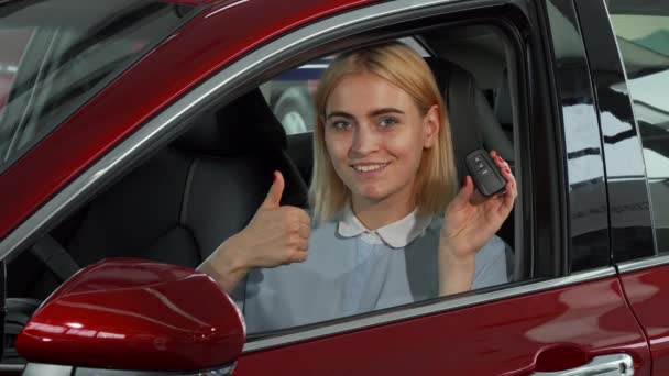 Happy female driver showing her car keys and thumbs up