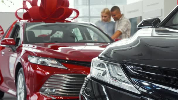 Young couple examining cars for sale at the dealership