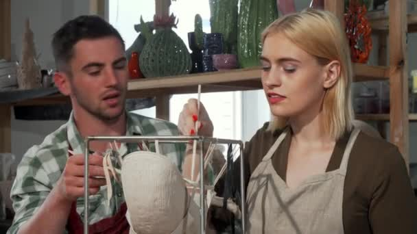 Professional potter helping his female student at the workshop