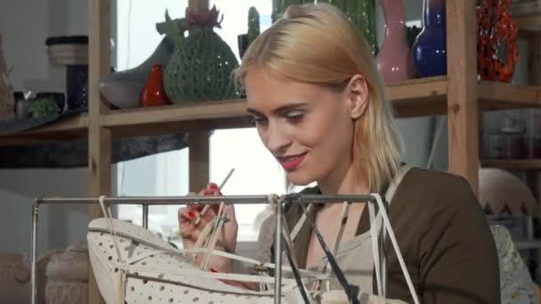 Beautiful female sculptor working at her ceramic store