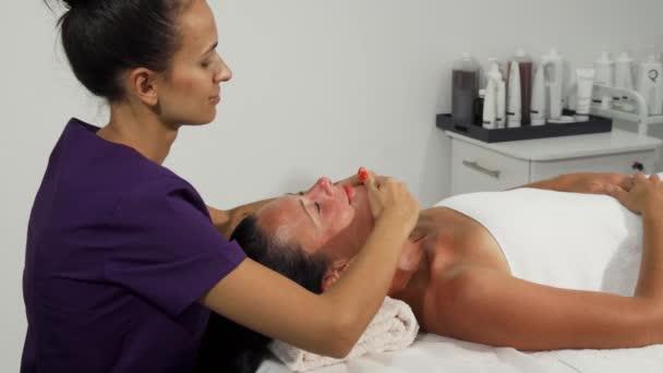 Terapeut provádí masáž obličeje pro zralé ženy