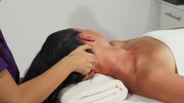 attraktive reife Frau entspannt sich bei einer Kopfmassage