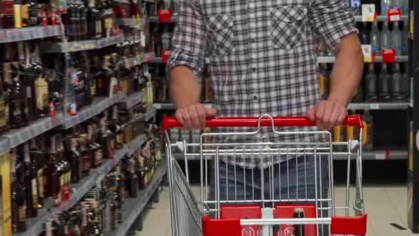 Muž s nákupním vozíkem v supermarketu