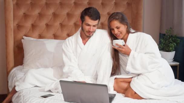 Mladý pár s kávou v posteli při používání notebooku. Nádherná žena, směje se při pití kávy v posteli s manželem. Krásný veselý člověk a jeho žena společně pomocí přenosný počítač v hotelovém pokoji
