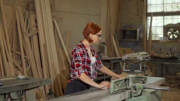 Ženské tesař pomocí elektrických nástrojů na její workshop