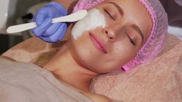 glückliche Frau bekommt Gesichtsbehandlung in der Schönheitsklinik