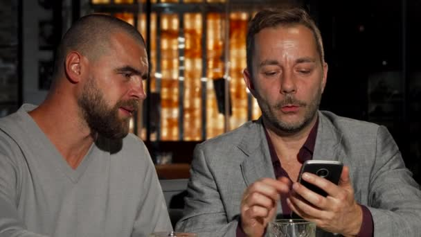 Mature man showing his friend something on smart phone while dronking whiskey
