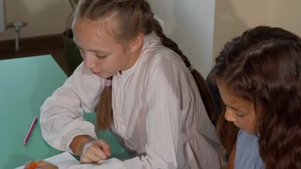 Two little schoolgirls coloring together during art class
