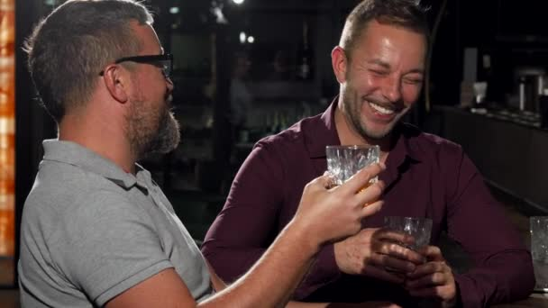 Two friends laughing to the camera while having drinks together