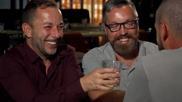 Zralé šťastný muž opékání s jeho skleničku na whiskey, usmívající se na kameru