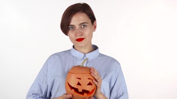 Krásná žena s červenými rty šťastně se usmívala, držení Halloween dýně