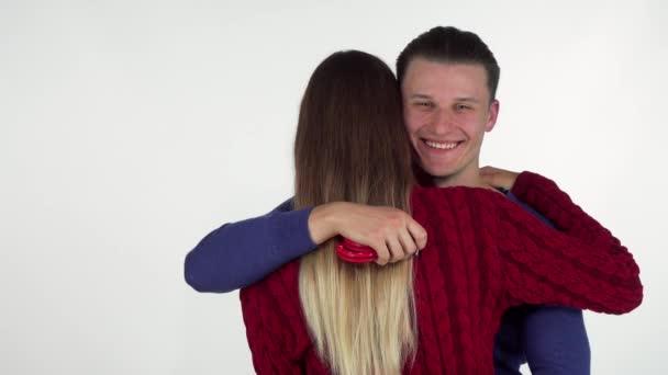 Handsome Mann umarmt seine Freundin, hält Sex-Spielzeug Handschellen hinter ihrem Rücken