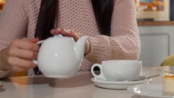 Žena nalil aromatického čaje do její pohár v kavárně