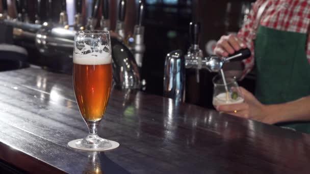 Vynikající řemeslné pivo na stole, barman pracuje na pozadí