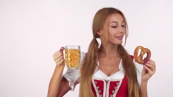 hinreißend sexy deutsche Kellnerin im Dirndl, die Bier trinkt und leckere Brezeln in der Hand hält