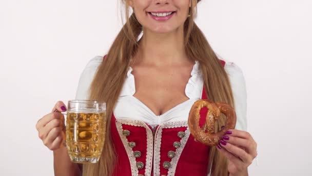 Unerkennbar sexy Oktoberfestmädchen im Dirndl lächelnd, Bier und Brezel in der Hand