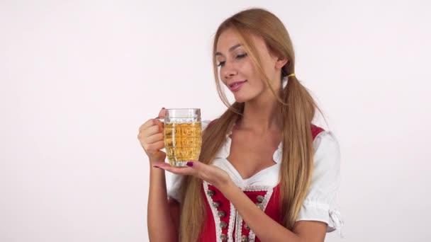 attraktive, fröhliche deutsche Frau im Oktoberfestkostüm serviert einen Bierkrug
