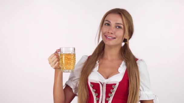 Charmante sexy Bayerin mit Bierkrug, die auf den Kopierraum zeigt. schönes fröhliches Oktoberfestmädchen, das isoliert Bier serviert. Service, Kneipe, Bar, Food Festival Konzept