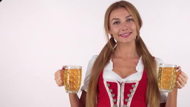 Schönes Oktoberfest-Mädchen bläst Küsse in die Kamera und hält zwei große Bierkrüge in der Hand