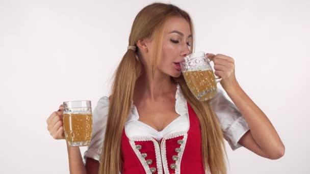 sexy Bayerin trinkt Bier aus zwei Krügen