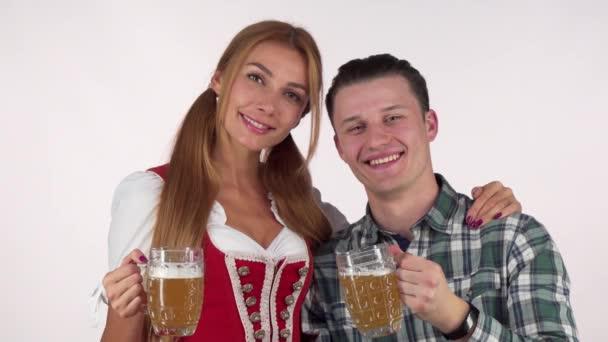 glückliches Oktoberfest-Paar klimpert mit Bierkrügen, lächelt sich an