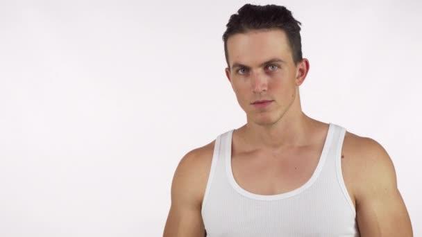 Svalnatý mladík protahuje jeho biceps zuřivě při pohledu do kamery