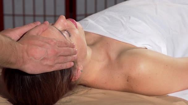 Žena přijímá, relaxační masáž hlavy v lázeňském centru