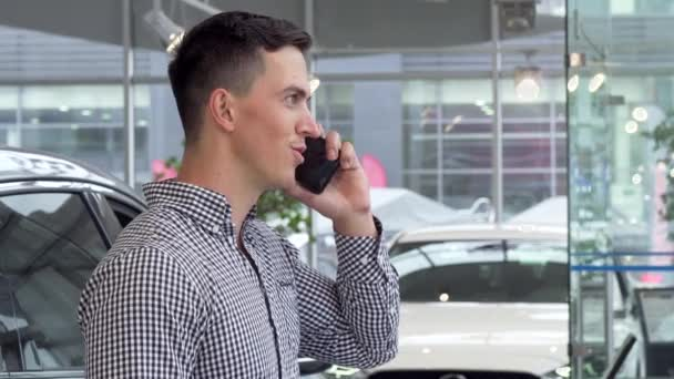 Excited man smiling, holding car keys at the dealership, talking on the phone