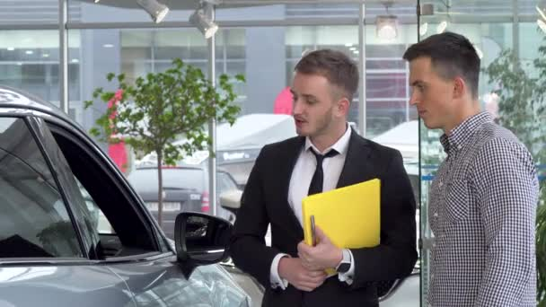 Friendly car dealer helping his male customer choosing automobile to buy