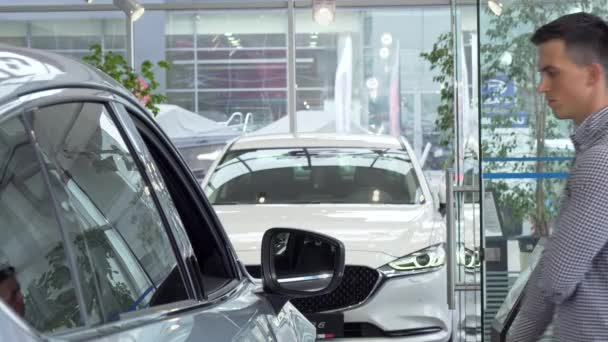 junger Mann reibt sich nachdenklich das Kinn und wählt ein neues Auto beim Händler